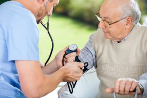 Male CNA checking blood pressure of senior man at nursing home