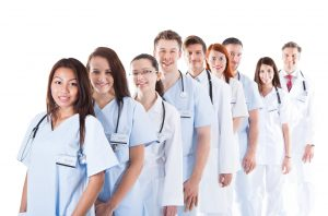 Long receding line or queue of smiling doctors and nurses in white uniforms wearing stethoscopes around their necks isolated on white ** Note: Shallow depth of field